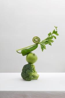 新鮮な緑の野菜と果物の白いテーブル。平衡浮遊食物