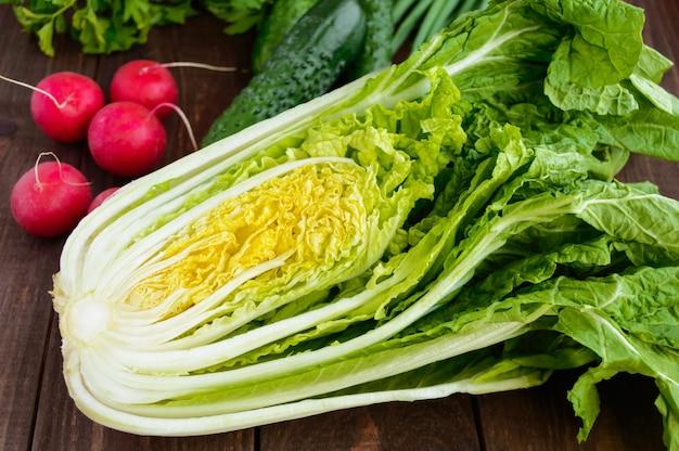 新鮮な緑の野菜(キャベツ、きゅうり)、ねぎ、パセリ、大根の木の背景に。サラダ用。