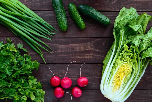 Fresh green vegetables (cabbage, cucumbers), green onions, parsley and radish on wooden background. for salads. top view