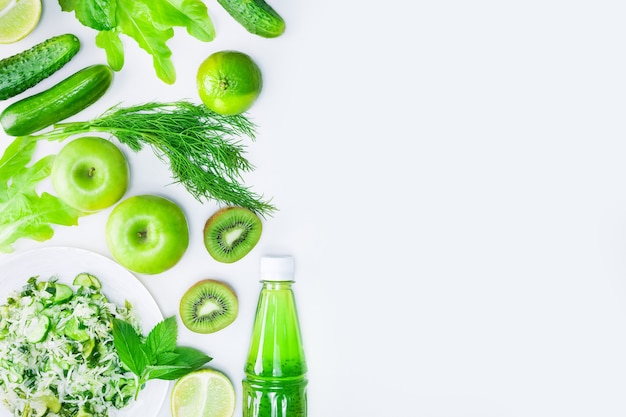 Fresh green vegetables, fruits and green smoothie in bottle. top view with copy space. detox, diet or healthy food concept