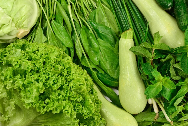 Fresh green vegetables and herbs as a background.