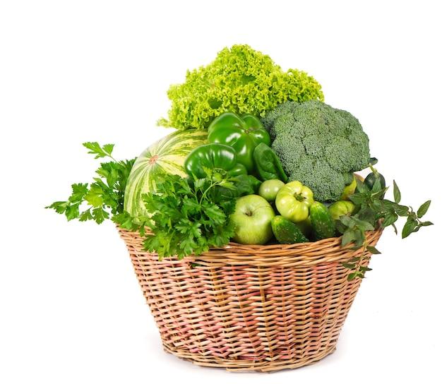 흰색 바탕에 고리 버들 세공 바구니에 신선한 녹색 채소