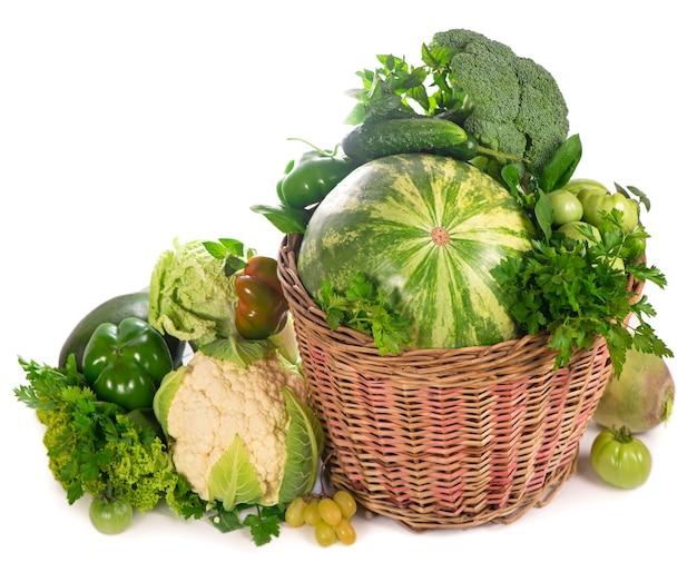 Свежие зеленые овощи в плетеной корзине на белой поверхности