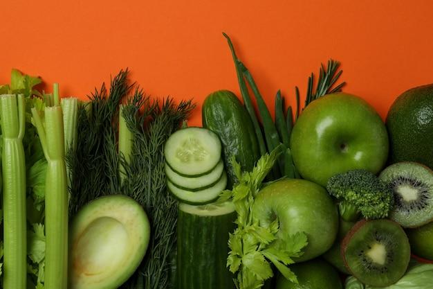 Свежие зеленые овощи на оранжевом фоне