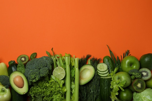 Fresh green vegetables on orange background