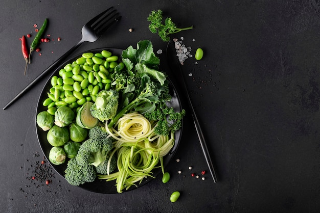 Fresh green vegetables with herbs and spices on a dark