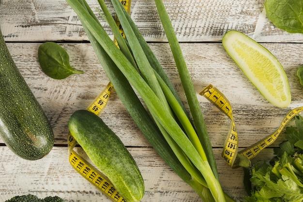 Свежие зеленые овощи с рулеткой на деревянном фоне