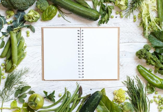木製のテーブルトップビューのノートブックと新鮮な緑の野菜