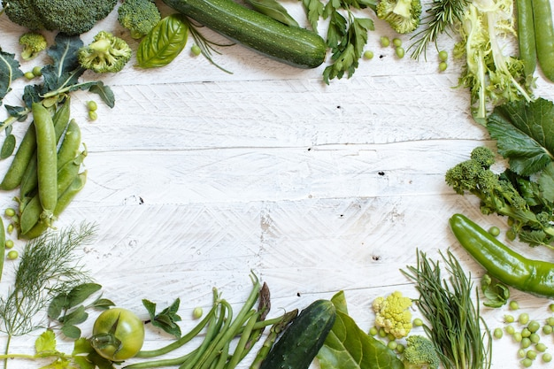 Fresh green vegetables on a wooden table top view