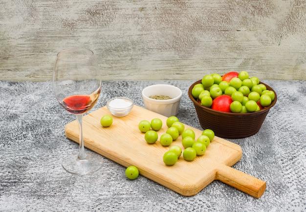 Свежая зелень и персики в коричневой миске и разделочной доске с небольшим кусочком соли и сушеным протертым тимьяном, немного красного вина на гранжевой стене и земле