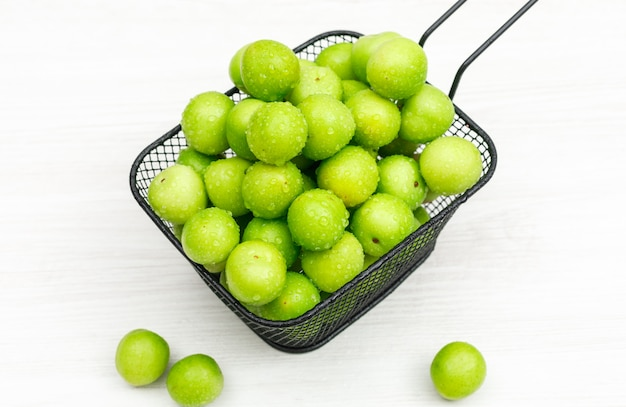 Fresh greengages in a black colander on white wood plank. high angle view.
