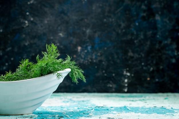 明るい青色の机の上のプレート内の新鮮な緑
