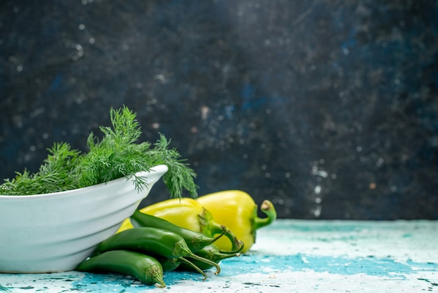 Verdure fresche all'interno del piatto con peperoni verdi e peperoni piccanti su blu brillante
