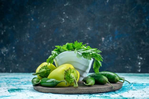 Свежая зелень изолирована внутри тарелки вместе с зеленым сладким перцем и острым перцем на ярко-синем