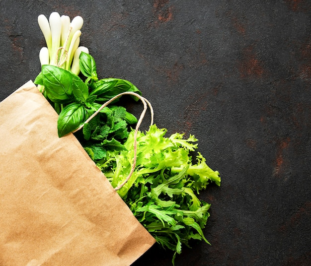 Fresh greens in a paper bag on a black surface