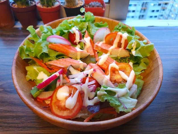 Салат из свежей зелени с крабовой палочкой и заправкой для салата в миске на деревянном столе