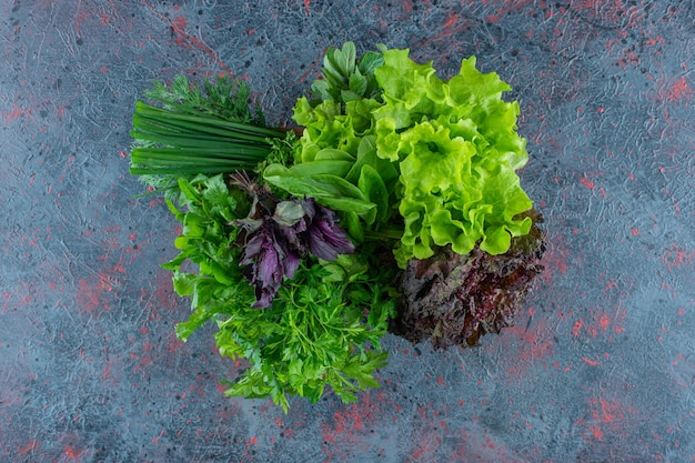 Fresh greens in a wooden box, on the marble background.