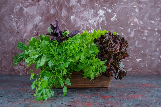 Fresh greens in a wooden box on the marble surface
