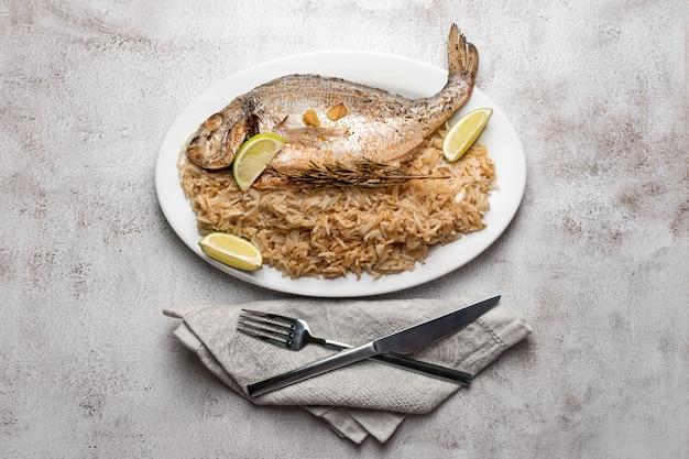 Свежая рыба дорадо или морского леща на гриле с лимоном и розмарином, подается с рисом.