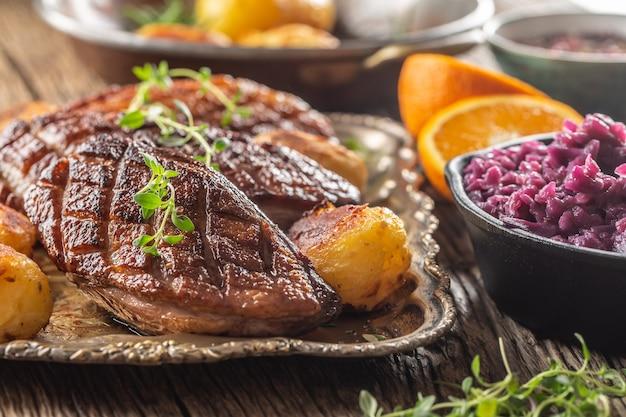 Свежие утиные грудки на гриле, подаются с жареным картофелем и красной капустой.
