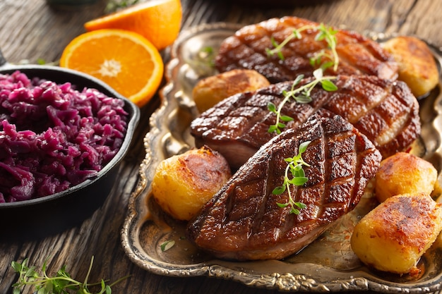 Fresh grilled duck breasts served with roasted potatoes and red cabbage.