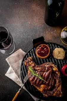 Стейк из говядины со свежим мясом на гриле с зеленью и специями из красного вина. темный ржавый фон