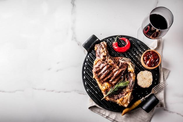 Стейк из свежего мяса на гриле с красным вином, зеленью и специями