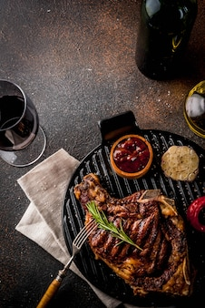 Fresh grilled meat beef steak with with red wine herbs and spices.  dark rusty background