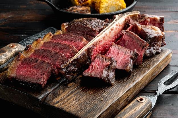 焼きたての肉。グリルしたビーフステーキミディアムレアセット、tボーンまたはポーターハウスカット、木製のサービングボード、古い暗い木製のテーブルの背景