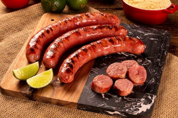 Свежая колбаса пепперони на гриле. жареная колбаса пепперони на деревянной доске. вид сверху.