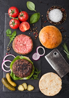 Fresh grilled and raw minced pepper beef burger on stone chopping board with buns onion and tomatoes. salty pickles and basil. top view
