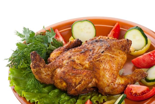 Свежий жареный цыпленок с огурцом, сырыми помидорами на тарелке с листовым салатом, изолированным на белом фоне