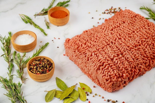 Fresh ground beef with spices and rosemary on wooden background.