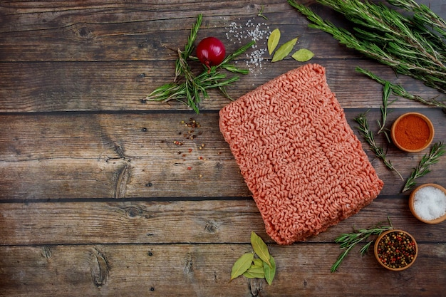 Fresh ground beef with spices and rosemary on wooden table.