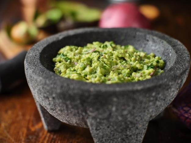 Fresh guacamole in stone molcajete