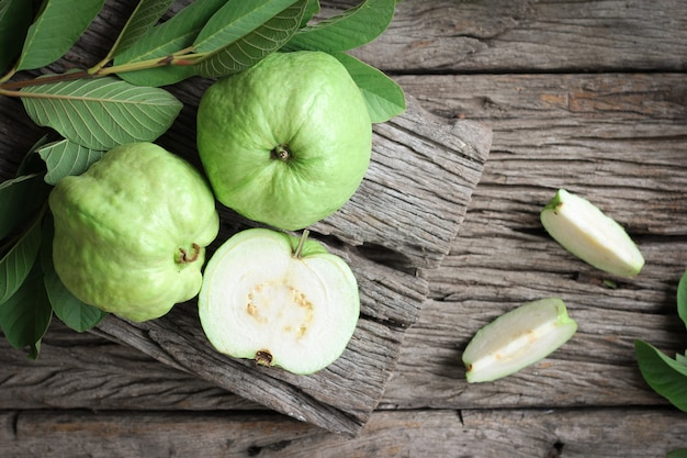 Fresh guava with green leaves on wooden background.