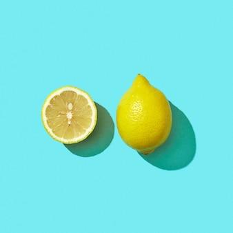 影とテキストのためのスペースの反射と青い背景の上の新鮮な半分と全体の有機レモン。モヒートの材料。上面図