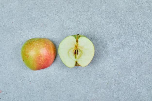 Mela fresca tagliata a metà su grigio.
