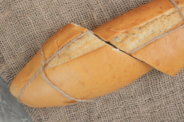 Mezzi tagli di pane freschi legati con corda su tela. foto di alta qualità