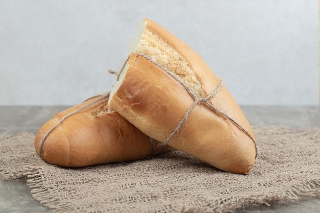 黄麻布にロープで結んだ焼きたてのパンのハーフカット。高品質の写真