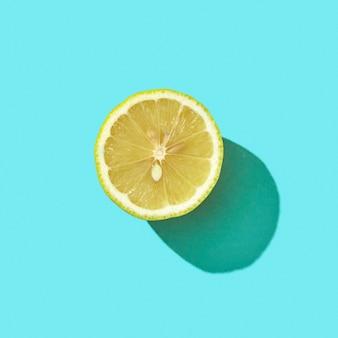 影とテキスト用のスペースの反射と青い背景に新鮮なハーフオーガニックレモン。モヒートの材料。上面図