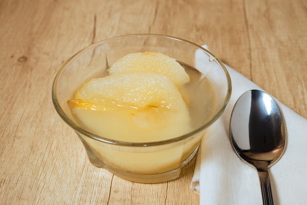 Fresh half pears served with sweet syrup. wooden table background.