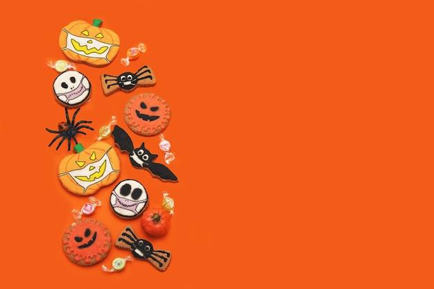 オレンジ色の背景に新鮮なハロウィーンのジンジャーブレッドクッキーたくさんのジンジャービスケットのトリックオアトリート