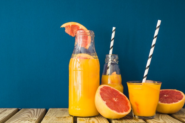 Fresh halved grapefruit and juice in the different container on table
