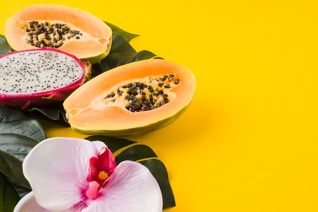 Fresh halved papaya and dragon fruit with orchid flower and leaves on yellow backdrop