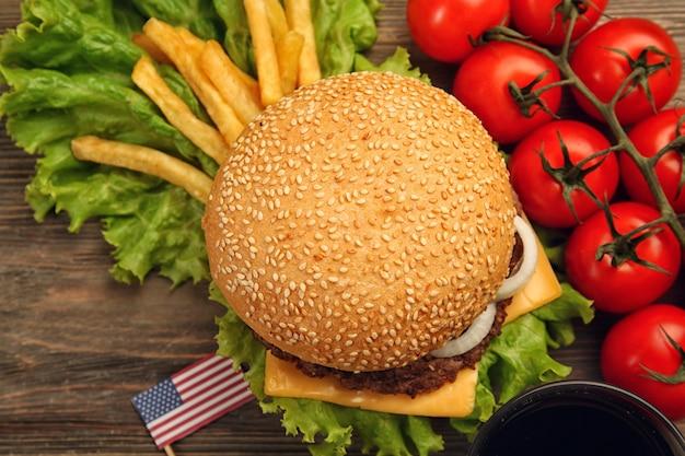 Свежий гамбургер с помидорами на деревянном столе