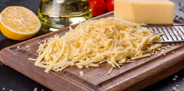 暗いコンクリートの背景に木製のまな板の大きなおろし金ですりおろした新鮮なハードチーズ