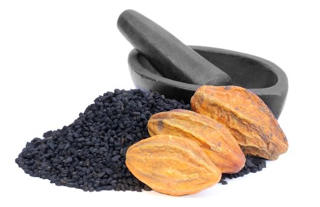 Свежие семена харитаки и чернушки или черный тмин с каменной чашей для приготовления лечебных трав
