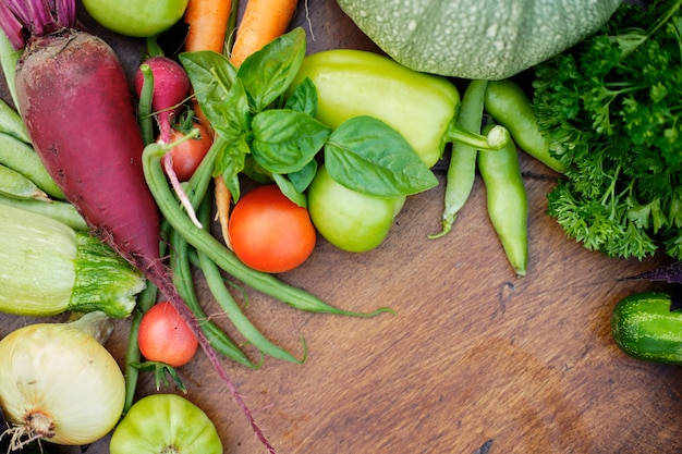 Fresh harvest from the gardens on wooden chalkboard from above.