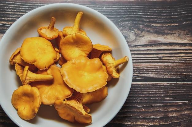 Свежий урожай грибов лисичек в белой миске на деревянном столе